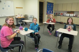 Four 6th grade students learn to knit.