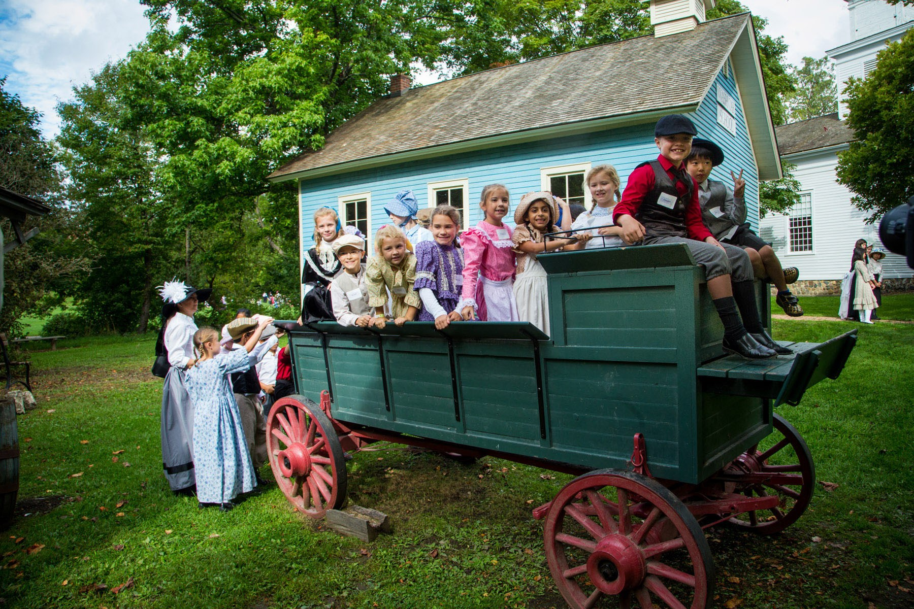 Third graders in Victorian garb pose for a Heritage Festival photo in an old time wagon.