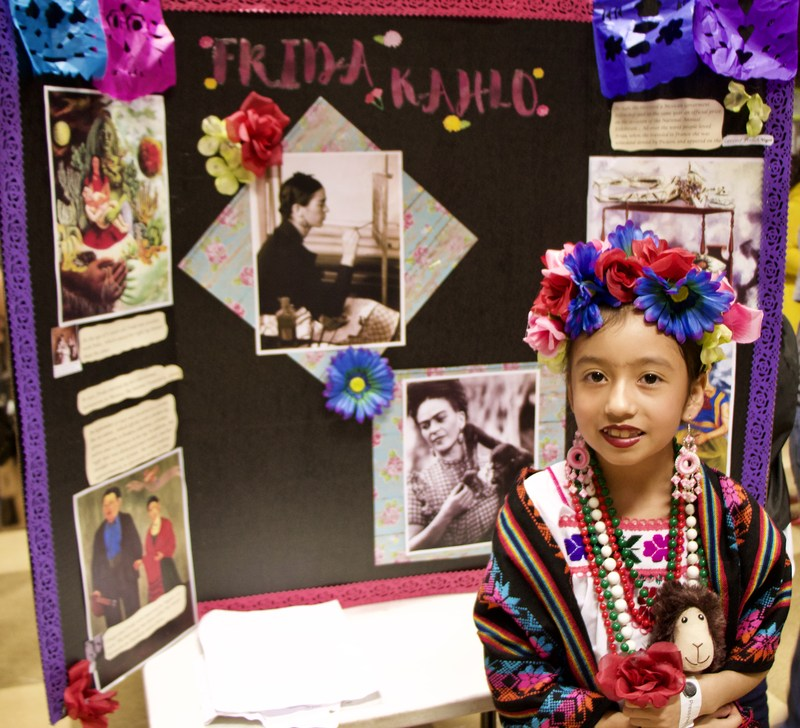 Student Dressed as Frida Kahlo stand in front of their exhibit
