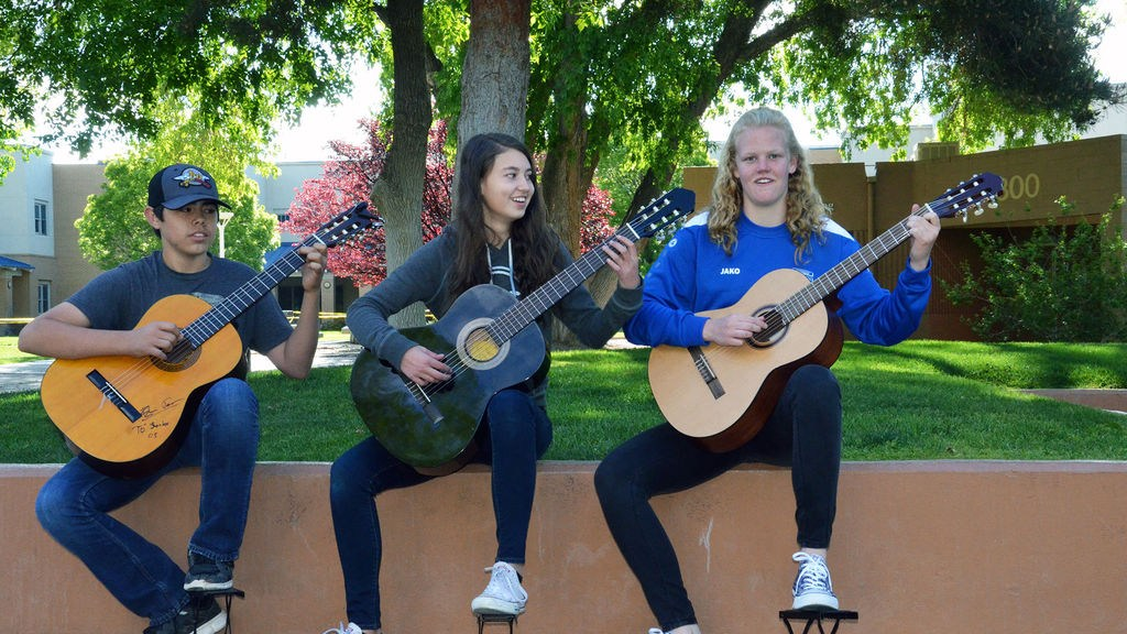 Three upper school students play guitar on the Quad