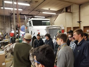 High School students gathered in a welding shop filled with machinery and a diesel truck