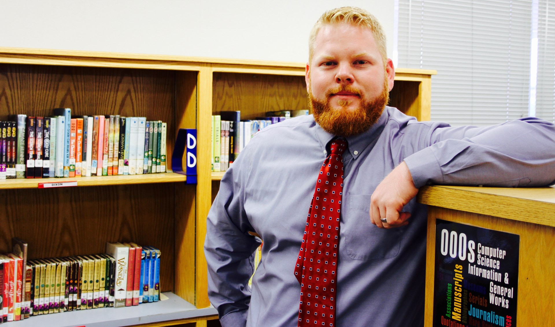 Principal standing in library with arm on book case