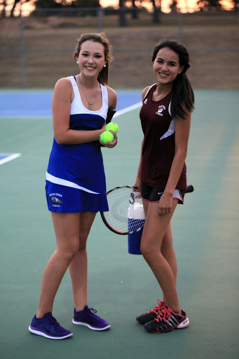 Two high school girls in tennis outfits standing together on tennis court holding rackets and balls