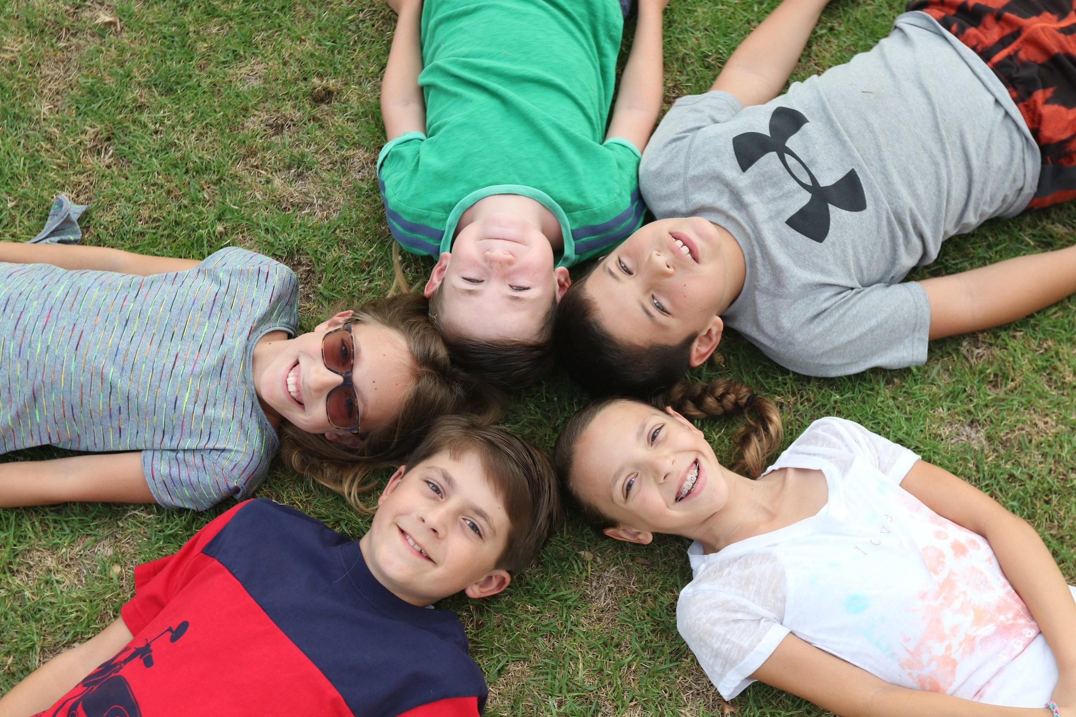 children laying on the grass looking skyward