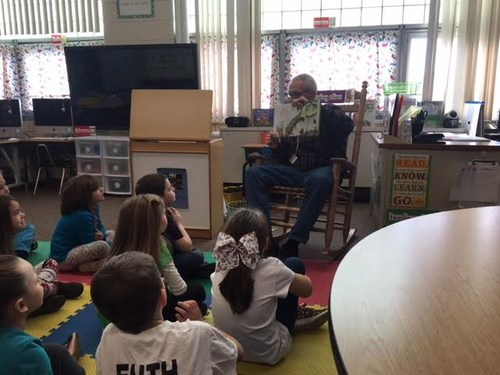 Adult reading to students.