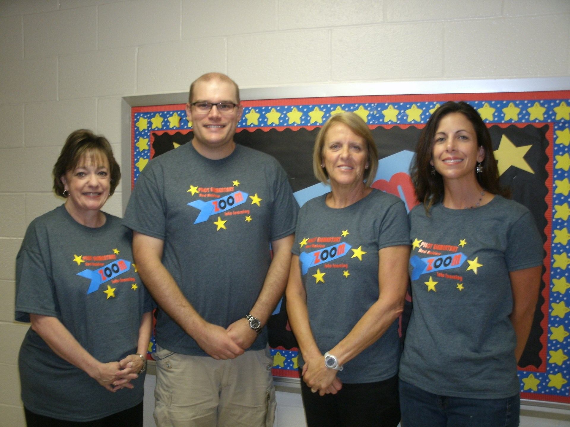Guidance, music, PE, and art teachers stand in front of a bulletin board.