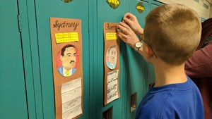 A 3rd grader posts his MLK project to his locker.