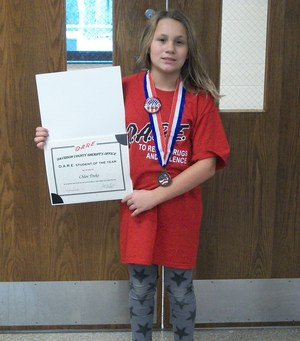 Students holding DARE certificate and wearing a medal around her neck.