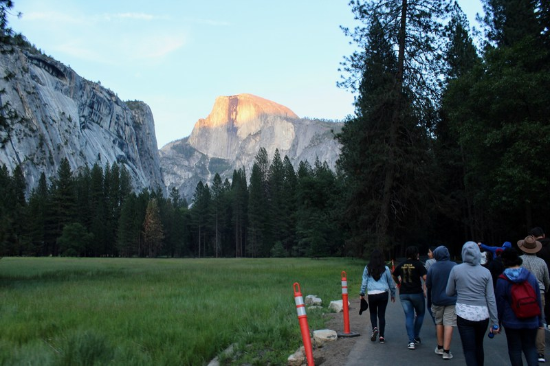 A group of students walks during sunrise at Yosemite National Park