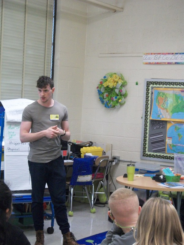 Hunter Mikles stands before a group of students.