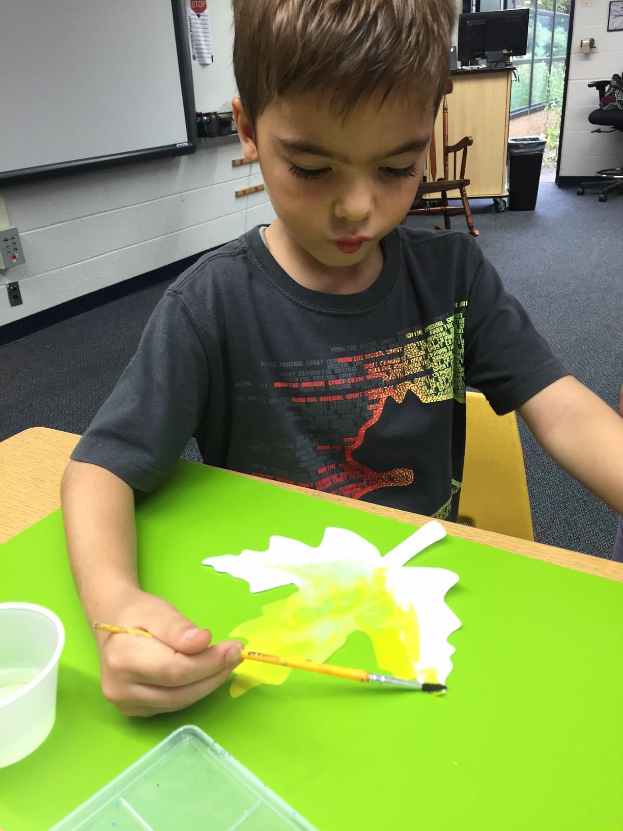 Boy painting a leaf.