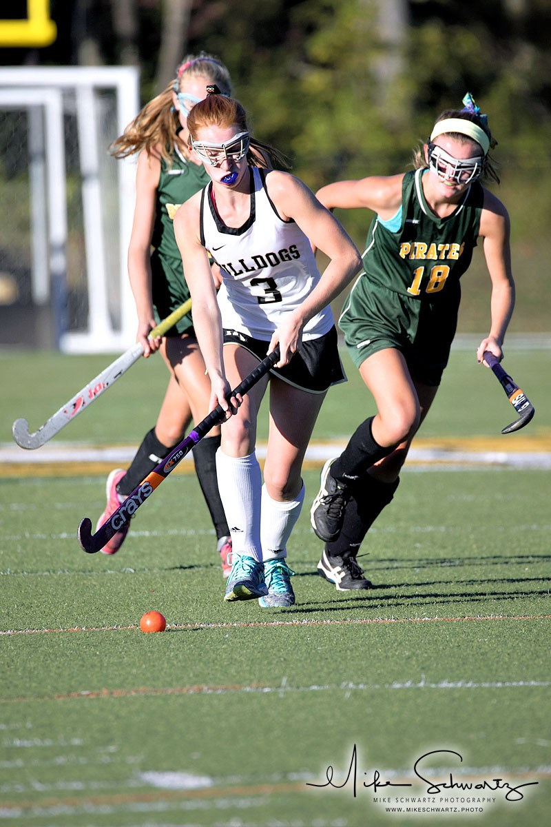 CHS girls field hockey player pursued by two opponents
