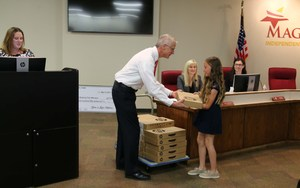 Glenn Addison passing out the Chromebooks during the school board meeting.jpg