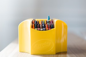 box of crayons in yellow holder