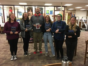 Students and a teacher standing in a row holding books