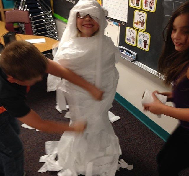 Student wrapped in paper.