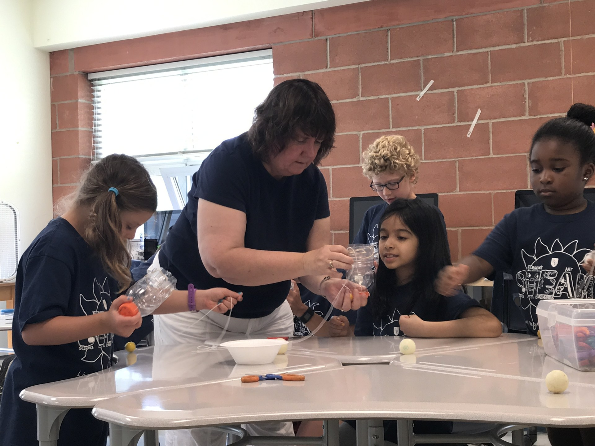 Teacher helping students during Summer STEAM