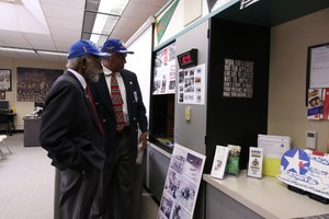 Tuskegee Airmen Theodore Lumpkin and Robert Porter looking at student's posters.