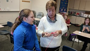 Mrs. Laws helps a student learn to crochet.