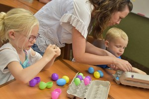 East Valley Elementary teacher helping kids count plastic eggs.