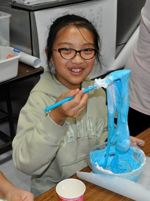 Foster Elementary School fifth-grader Genevieve Tran mixes up a plate of bright blue unicorn slime during the school's first STEAM Night.