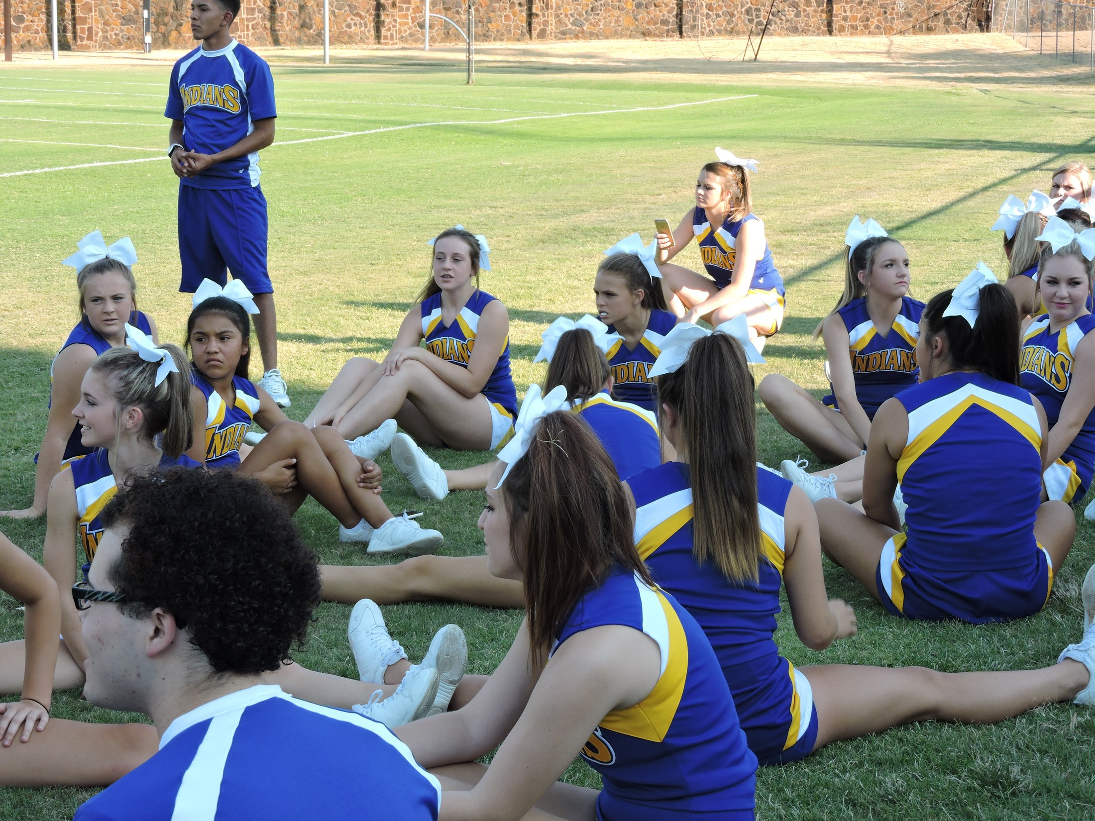 cheerleaders sitting on the field