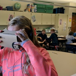 Maddie looks through Google Cardboard goggles to see Independence Hall.