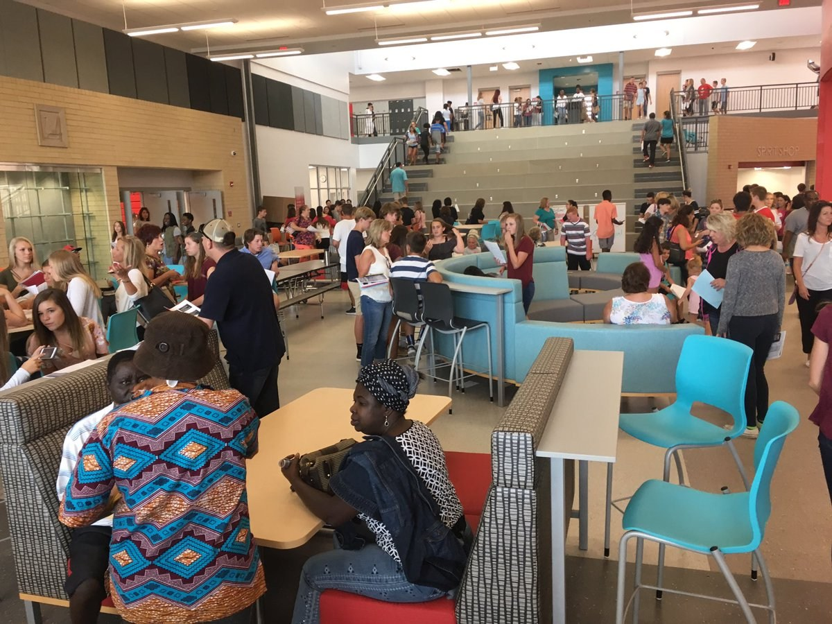 Freshman School students enjoying their new school during an orientation meeting. They are sitting around tables and talking.