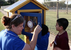 students stocking the little library with books.