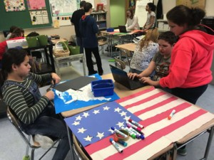 Three students sit around a desk with a construction paper flag depicting red and white stripes and a blue square with shite stars