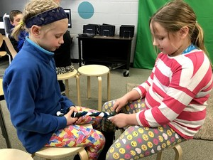 Charity Laker (l) and Olivia Rosenberg work together to make a braided chew toy for the animal shelter.