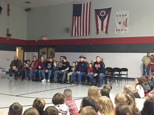 American Veterans sitting in chairs at a school assembly.