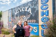 Monica Barragan and Roni Sustal in front of the Acacia Cougar wall painting