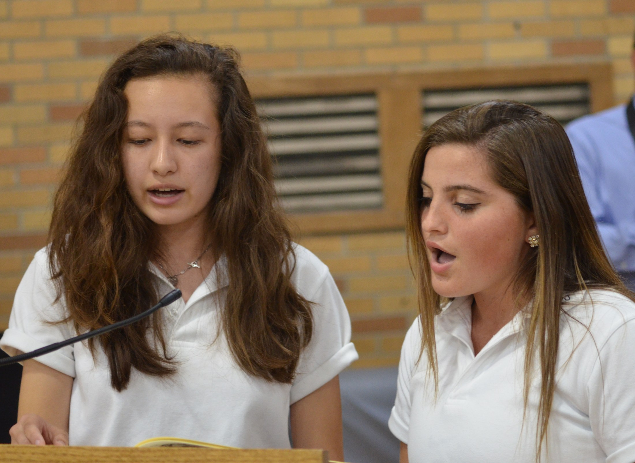 Two girl students sing song in mass
