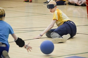 Camper trying to block a goalball from scoring