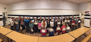 Students in a group showing their V.I.P. certificates.