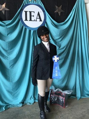 Picture of student in riding gear, holding her trophy.