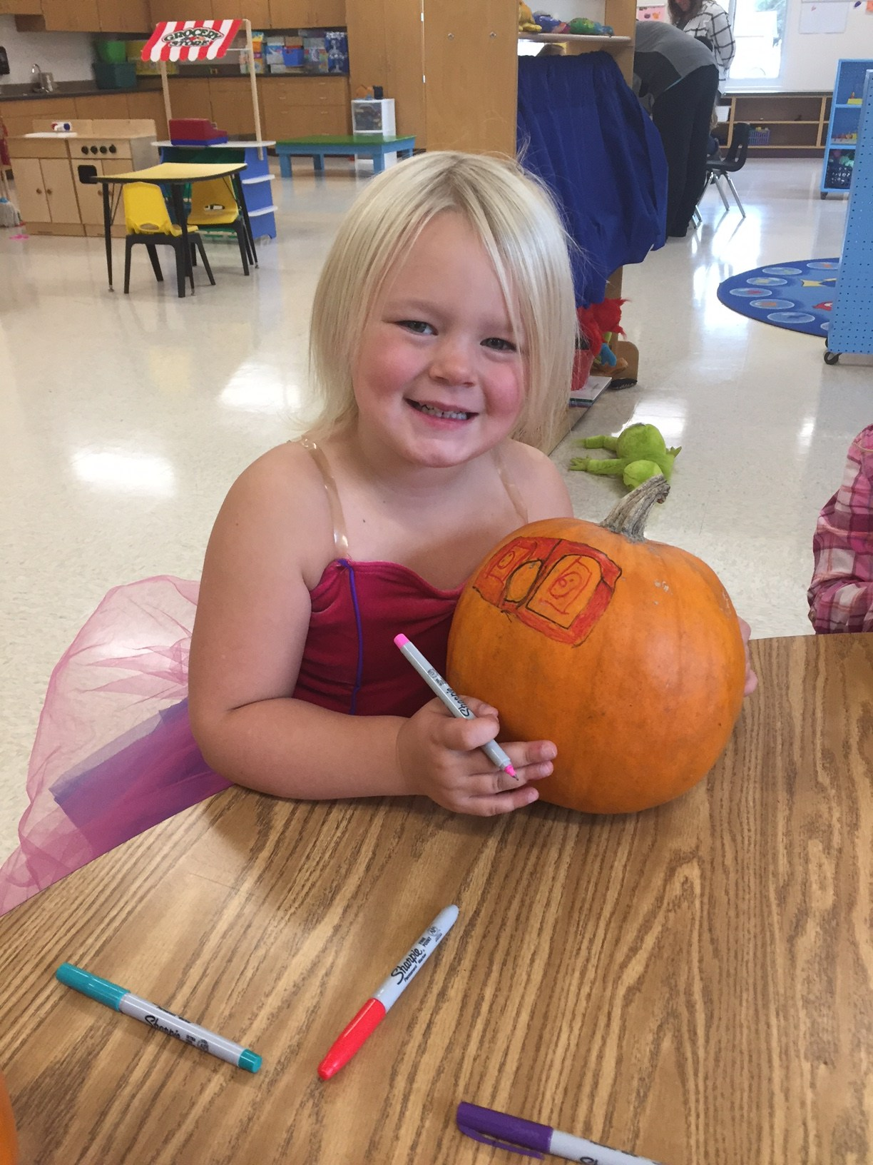 Coloring her pumpkin
