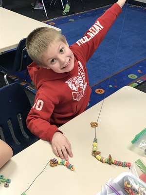 A student is all smiles making a necklace with 100 fruit loops.