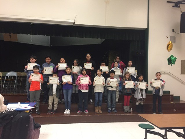 spelling bee contestants with certificates on stage