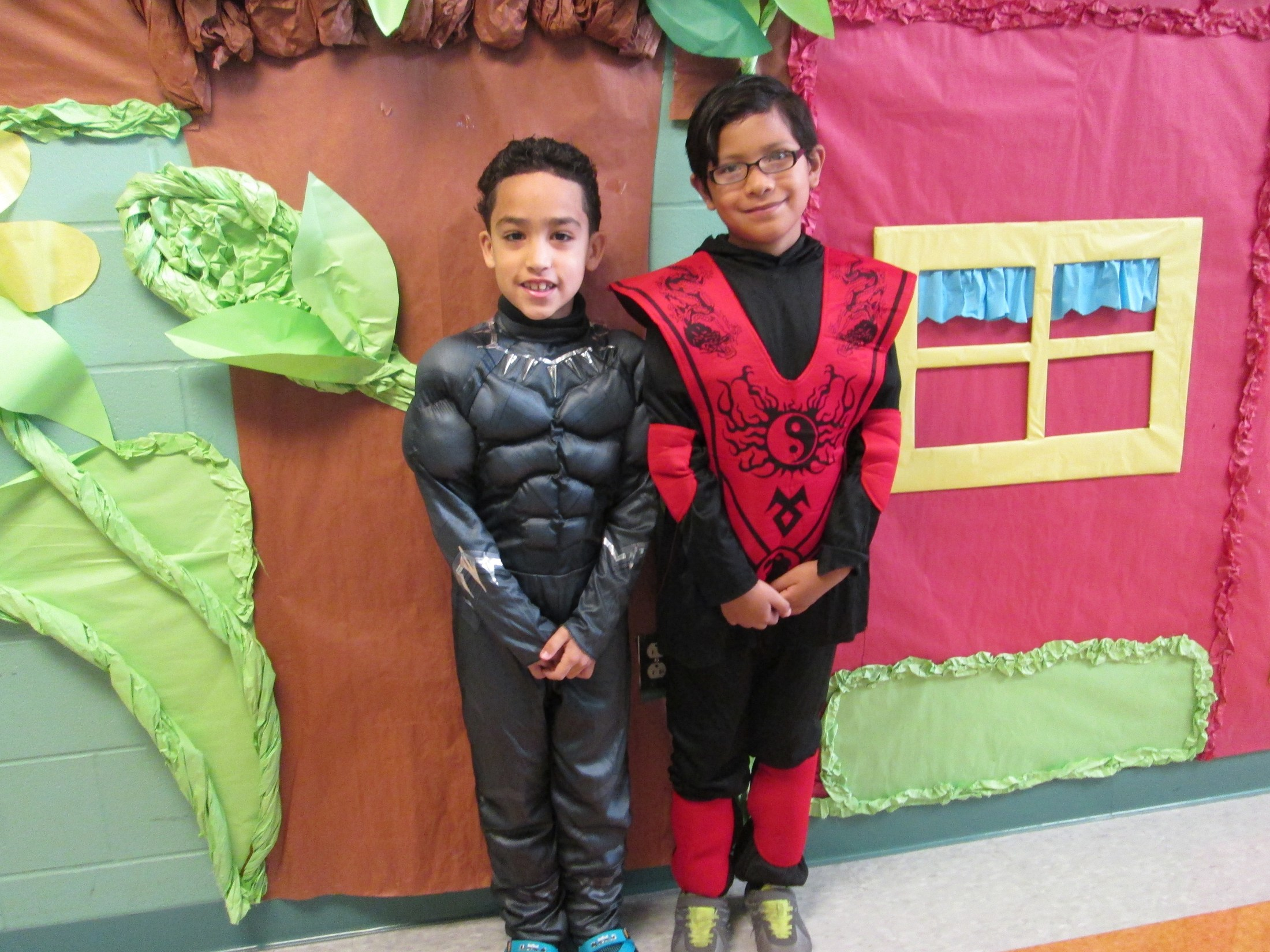 two boys showing of their superhero costumes