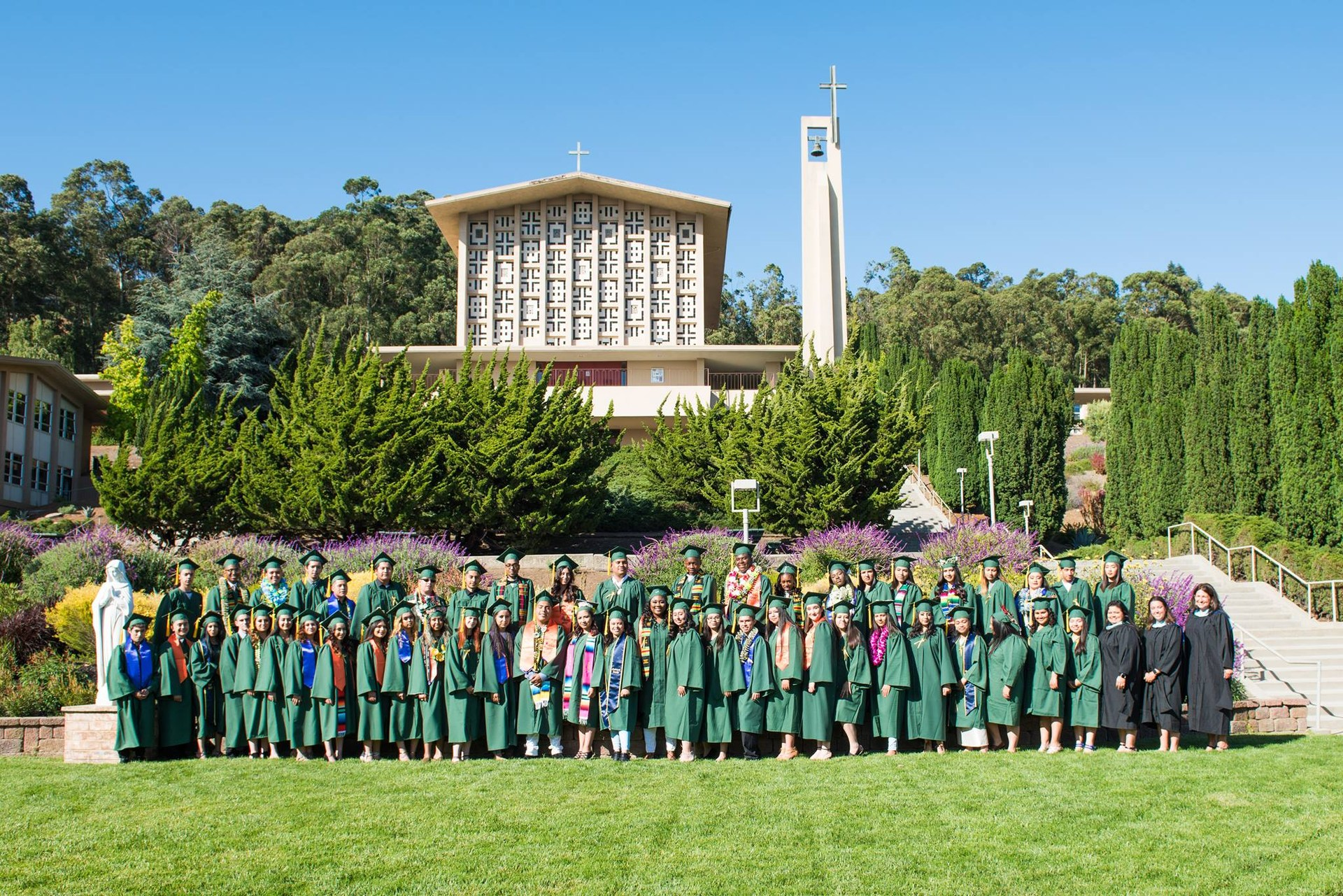 Graduating students in green caps and gowns