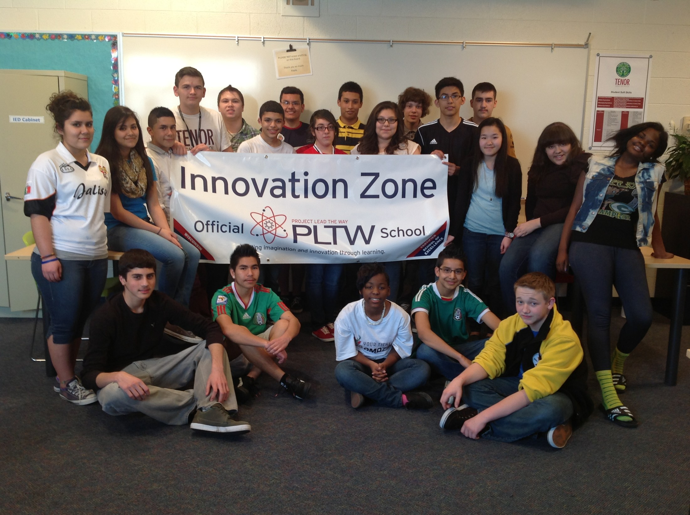 Students posing for picture by PLTW poster