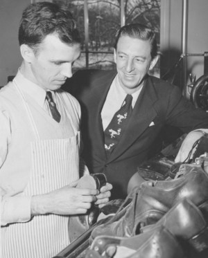 Visitor being shown shoe repairing by a veteran.