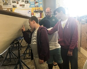 Students looking at a boat NYI students helped make
