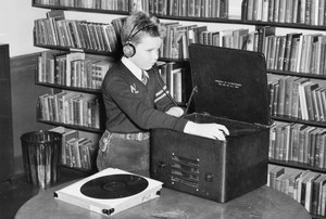 Young student with headphones listing to a talking book