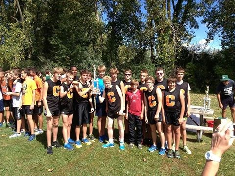 Photo of boys cross country team at regionals with trophy