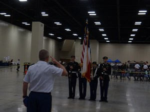 Four JROTC students holding flags while a military man salutes.