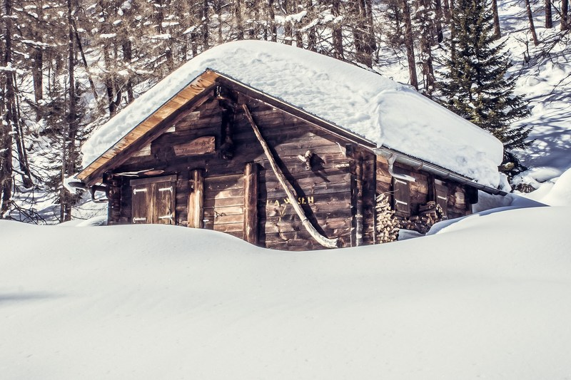 Image of a cabin in the woods covered in deep snow.