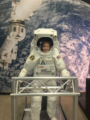 Katie climbed into a real space suit, which is quite large on her, to pose for a picture.